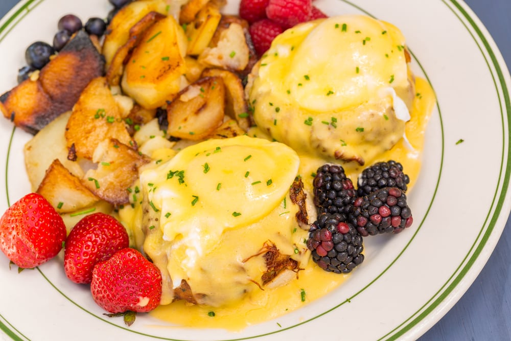 Crab cakes eggs benedict with potatoes and berries.